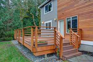 Home with half wood, half vinyl siding, and a beautiful wooden deck