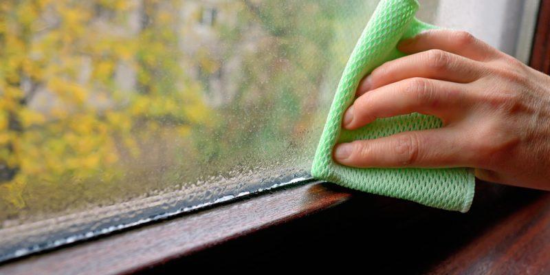 Window condensation, hand wiping away moisture